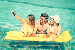 采取selfie的最好的朋友在与黄色的游泳池airbed 免版税库存照片