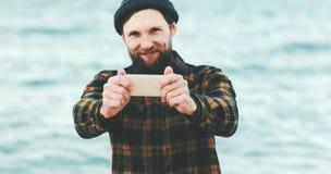 采取selfie的有胡子的人使用智能手机海上 免版税库存照片