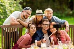 采取selfie的朋友在党在夏天庭院里 库存图片