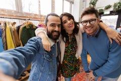 采取selfie的朋友在葡萄酒服装店 图库摄影