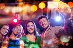采取selfie的朋友由在夜总会的智能手机 图库摄影