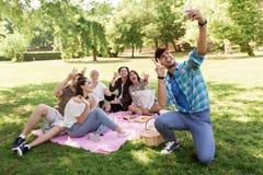 采取selfie的朋友由智能手机在野餐 库存图片