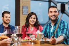 采取selfie的朋友由智能手机在餐馆 免版税库存照片