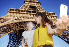 采取selfie的母亲和女儿游人反对埃佛尔铁塔 免版税库存图片