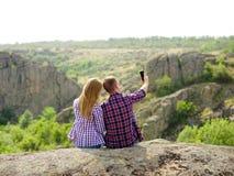 采取selfie的浪漫夫妇 拍摄在自然本底的旅客照片 概念查出的技术白色 复制空间 库存照片