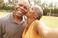 采取Selfie的浪漫资深夫妇在公园 免版税库存图片