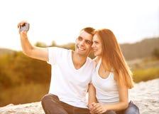 采取selfie的爱恋的夫妇在公园 免版税库存照片