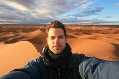 采取selfie的男性独奏旅客在撒哈拉大沙漠,摩洛哥 库存照片