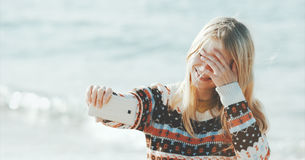 采取selfie的白肤金发的妇女使用智能手机海上 免版税库存图片