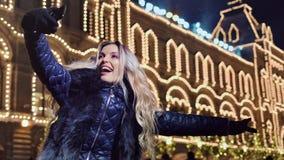 采取selfie的笑的妇女使用智能手机在照亮的圣诞节门面房子背景 股票录像
