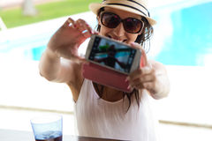 采取selfie的美丽的女孩在游泳池 库存照片