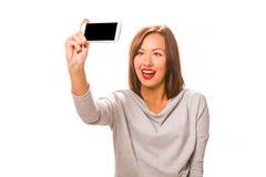 采取selfie的美丽的少妇使用智能手机 图库摄影