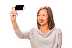 采取selfie的美丽的少妇使用智能手机 库存图片