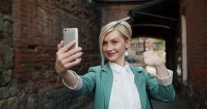 采取selfie的美丽的年轻女人的慢动作户外与智能手机 股票视频