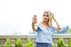 采取selfie的美丽的白肤金发的少妇在公园 免版税库存照片