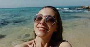 采取selfie的美女使用在海滩的电话 股票录像