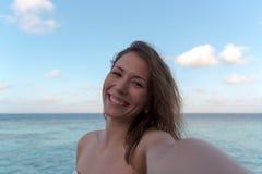 采取selfie的蜜月的年轻女人 作为背景的海 免版税图库摄影