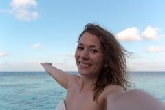 采取selfie的蜜月的年轻女人 作为背景的海 库存照片