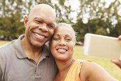 采取Selfie的资深夫妇在公园 免版税图库摄影