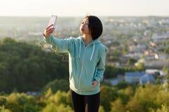 采取selfie的运动服的可爱的年轻日本妇女室外在绿色夏天公园公园使用她的电话和 库存照片