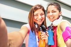 采取selfie的运动的女朋友在断裂期间在跑的训练 库存图片