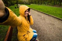 采取selfie的逗人喜爱的愉快的少妇在大风天 库存图片