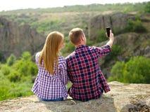 采取selfie的逗人喜爱的浪漫夫妇 拍摄在自然本底的游人照片 青年和技术概念 库存图片