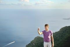 采取selfie的年轻人在海的一座山顶部 免版税图库摄影