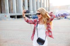采取selfie的年轻俏丽的妇女在正方形在城市 库存图片