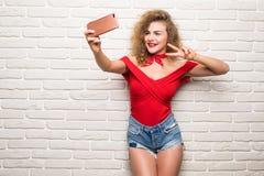 采取selfie聪明的电话照相机的女孩激发在白色砖办公室墙壁的愉快的微笑妇女 免版税库存照片