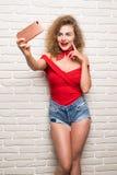 采取selfie聪明的电话照相机的女孩激发在白色砖办公室墙壁的愉快的微笑妇女 免版税图库摄影