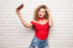 采取selfie聪明的电话照相机的女孩激发在白色砖办公室墙壁的愉快的微笑妇女 免版税库存图片