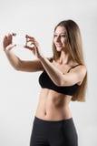 采取selfie,与智能手机的自画象的微笑的运动的女孩 免版税库存照片