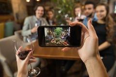 采取Selfie年轻商人小组饮料酒坐的餐馆表,朋友举行玻璃叮当声的女实业家 免版税库存照片