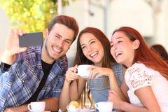 采取selfies的三个兴高采烈的朋友在咖啡馆 图库摄影