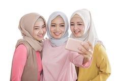 采取selfies的三美丽的兄弟姐妹使用移动电话照相机 免版税库存图片