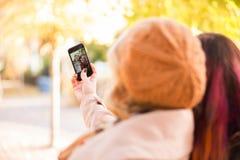 采取selfies的两个女孩在秋天公园 库存照片
