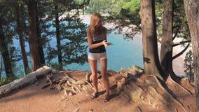 采取Selfies的美丽的少妇在边缘岩石背景海和杉木 股票录像
