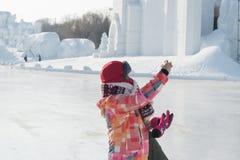 采取selfies -妇女伸出拍照片的手在哈尔滨雪节日结冰的寒冷 免版税图库摄影