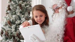 采取selfies wth的圣诞老人和愉快的小女孩在圣诞树旁边压片坐在扶手椅子 库存图片