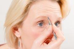 采她的眼眉的白肤金发的妇女特写镜头 免版税库存照片