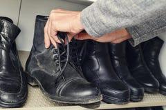采摘一双靴子从壁橱的年轻人 免版税图库摄影