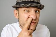 采摘他的在灰色背景的人鼻子 免版税库存照片