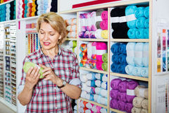 采摘各种各样的毛线的成熟高兴的妇女顾客 图库摄影