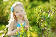 采摘在有机蓝莓农场的逗人喜爱的小女孩新鲜的莓果在温暖和晴朗的夏日 免版税库存图片