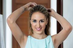 采摘她的头发用她的手的美丽的妇女 免版税库存照片