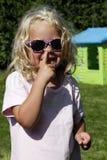 采摘她的鼻子的逗人喜爱的白肤金发的女孩 免版税库存图片
