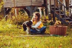 采摘愉快的儿童的女孩扮演小花匠在秋天和离开入篮子 季节性庭院工作 库存照片
