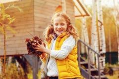 采摘愉快的儿童的女孩扮演小花匠在秋天和离开入篮子 季节性庭院工作 免版税库存照片