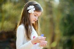 采摘春天的第一朵花可爱的小女孩在森林在美好的晴朗的春日 库存照片
